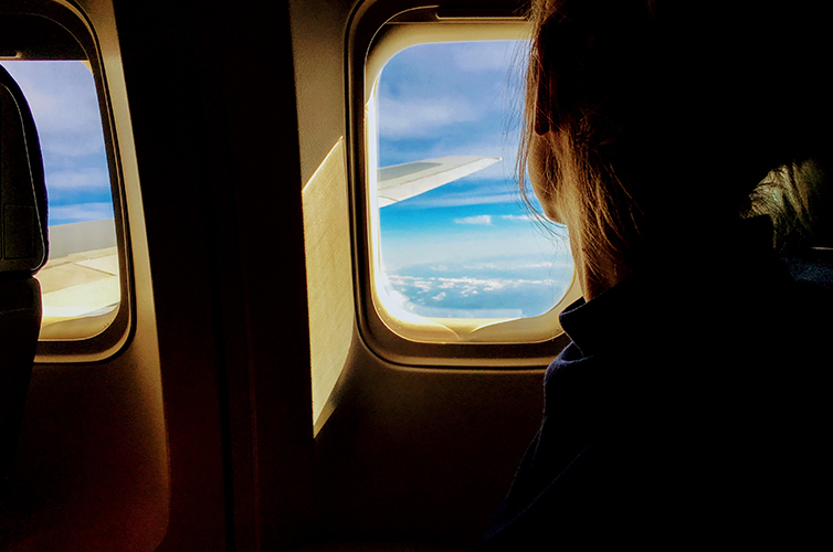 Young woman looking out of plane window to blue sky and clouds